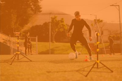 Young soccer player training with Tendo Sprint System by Tendo Sport to improve his speed in football field with team in background in orange