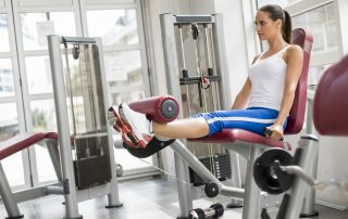 Pretty young woman athlete training legs in the gym performing seated leg curls while measuring her power and velocity with Tendo Unit by Tendo Sport to ensure she trains efficiently