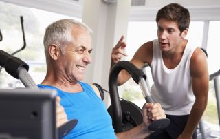 Middle Aged Man Being Encouraged By Personal Trainer In Gym while training with Tendo Sports machines and technologies