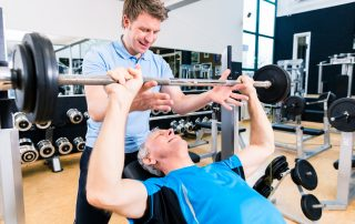 Trainer assisting senior man lifting barbell in gym while measuring his athletic performance via Tendo Unit by Tendo Sport to safely gain strength and fitness
