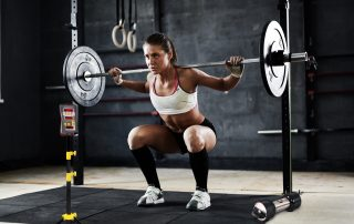 Woman athlete weight training with Tendo Unit by Tendo Sport while performing squats in a gym and measuring her athletic performance