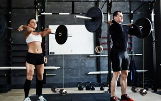 Active young man and woman athletes lifting heavy barbells while measuring their athletic performance via two separate Tendo Units by Tendo Sport being attached to barbells