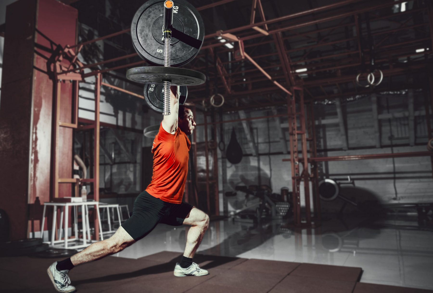 a man weight training in a gym with Tendo Barbell destabiliser while performing lunges to improve his balance and power - Tendo Sport