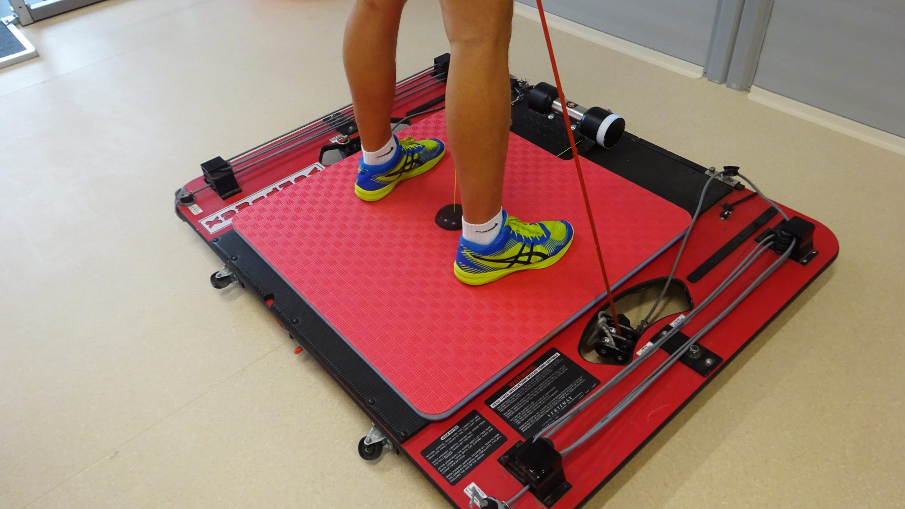 Male athlete performing jumps with Vertimax. Measuring power and velocity of legs using Tendo Unit and Tendo JumpMat with closeup on the mat