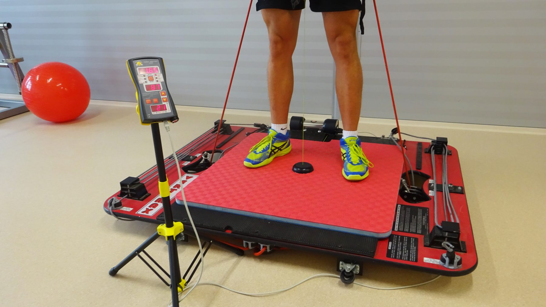 Athlete performing jumps with Vertimax. Measuring power and velocity of legs using Tendo Unit and Tendo JumpMat with detail On Tendo microcomputer unit